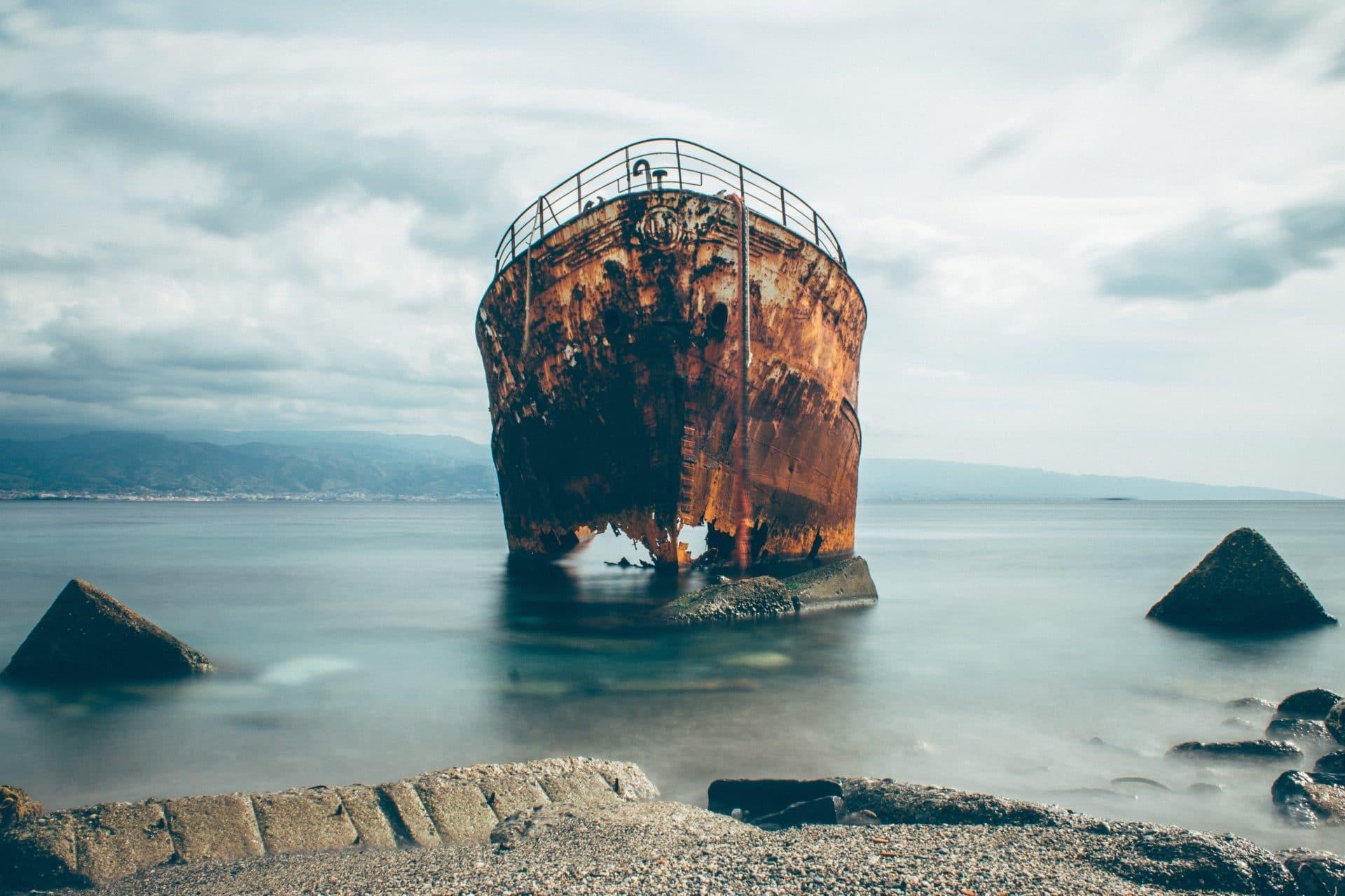 bateau rouillé échoué en bord de mer avec des troues dans sa coque