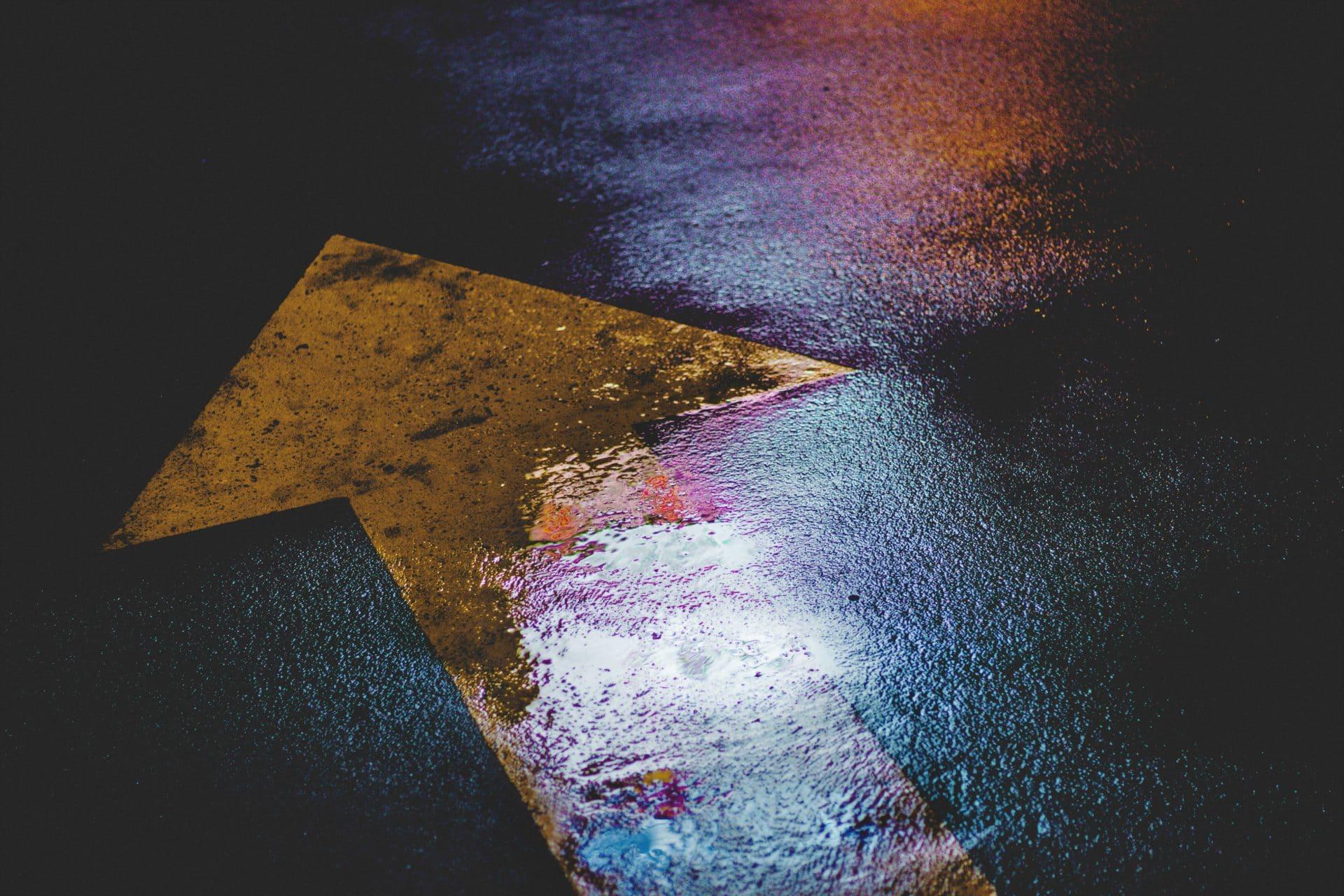 signalisation sur le sol humide d'une route avec une flèche jaune indiquant d'aller tout droit