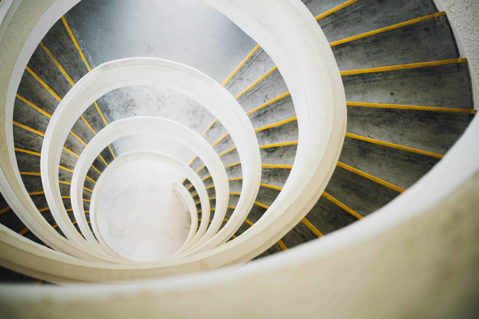 photo d'un escalier en colimaçon blanc pris du dessus prenant la forme d'un tunnel