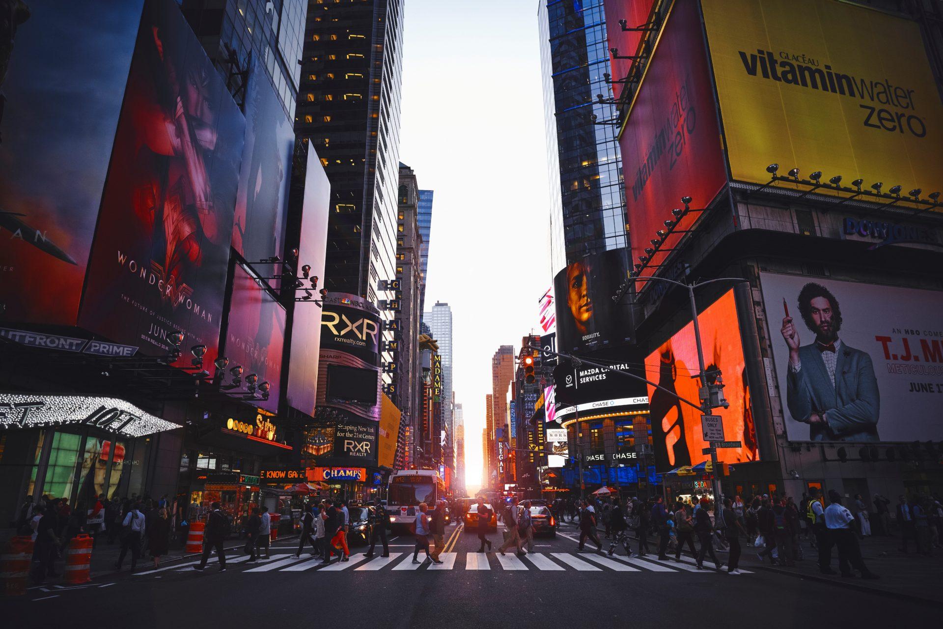 photo d'une rue de new york au levé du soleil avec tous les panneaux publicitaires allumé et des piétons traversant la route
