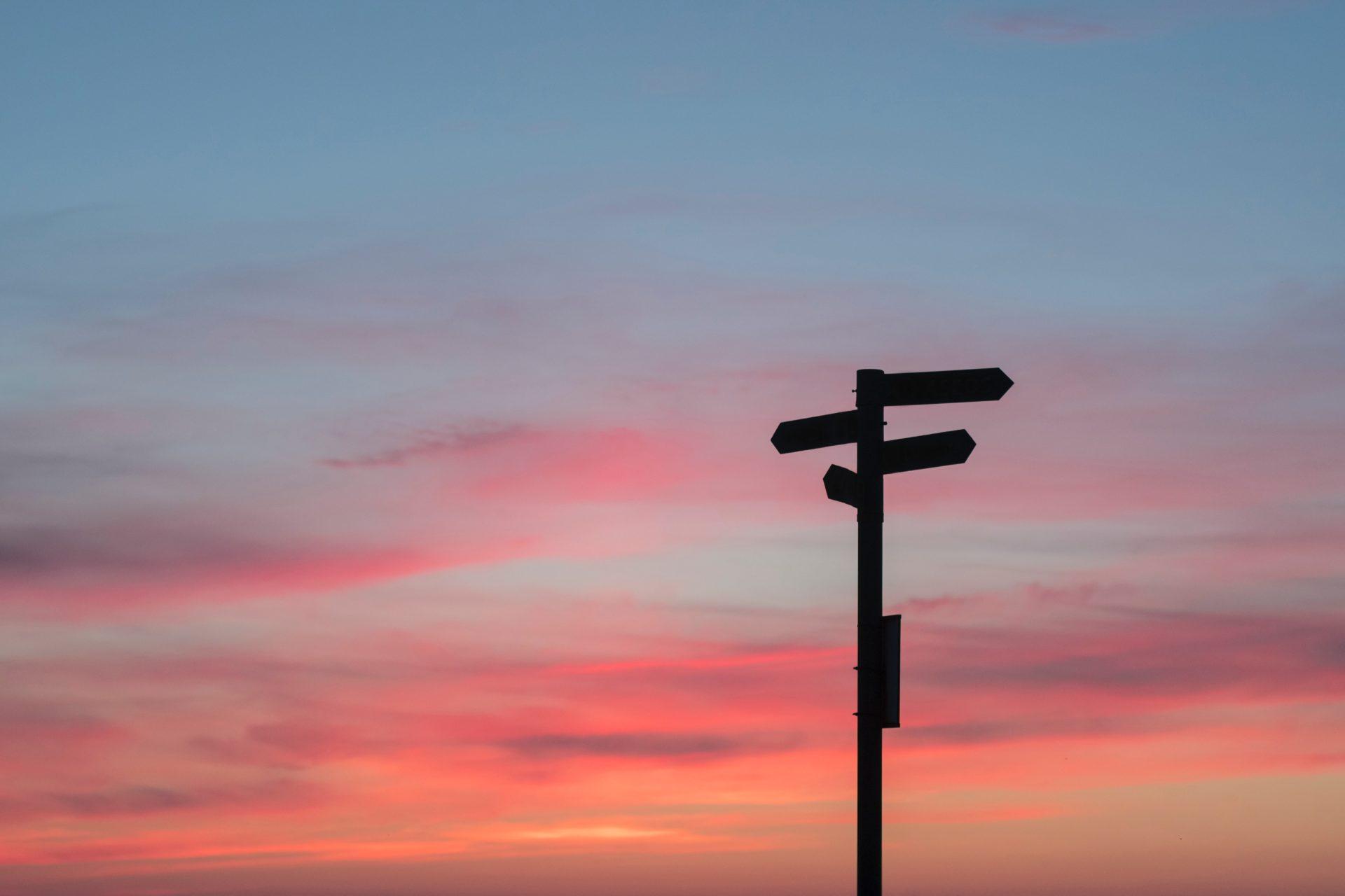 photo d'un coucher de soleil avec un ciel prenant des couleurs roses et un panneaux d'indication dirigeant vers différents chemins