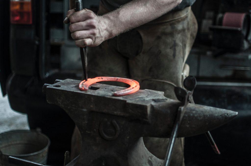 forgeron qui travail un fer de cheval ébouillanté et encore rouge sur une enclume avec des outils