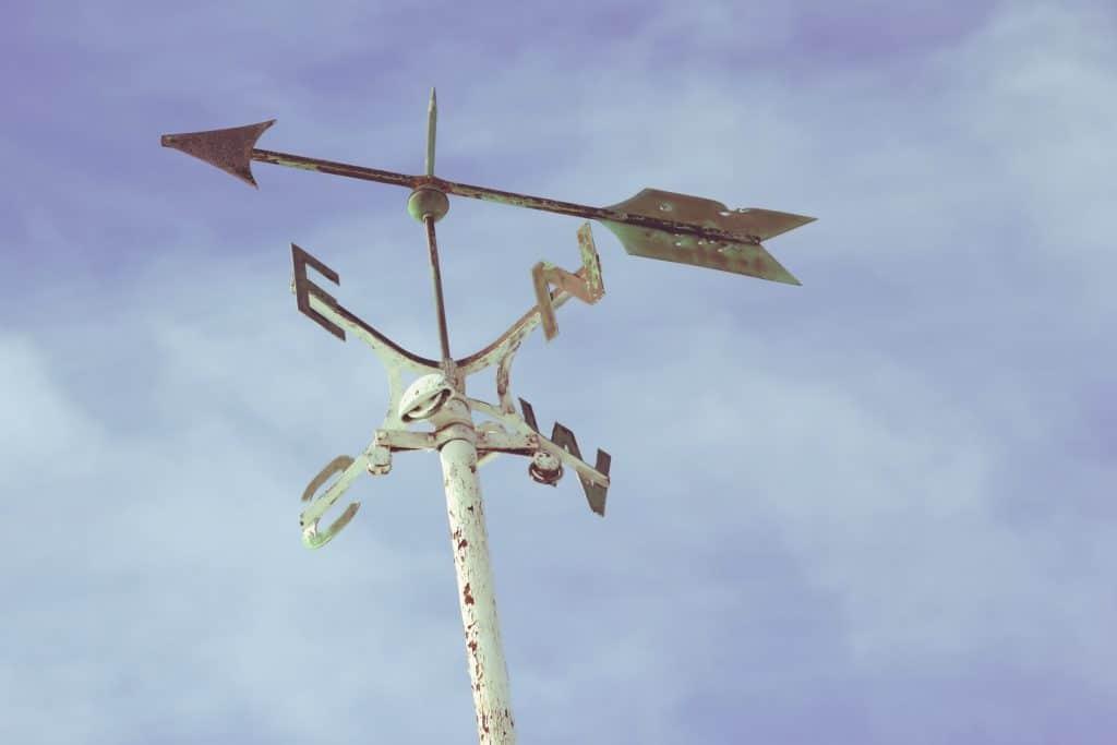 Photo d'une girouette rouillé avec la flèche indiquant un vent du sud est