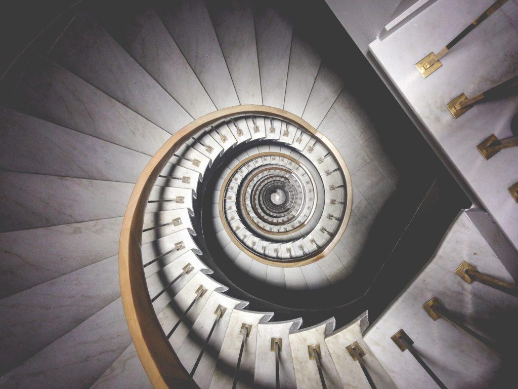 Photo d'un escalier en colimaçon composé de marche en marbre blanc représentant l'évolution du business modèle