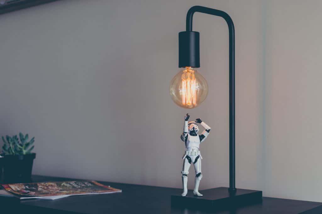 Figurine de stars wars placé en dessous d'une lampe avec une grosse ampoule