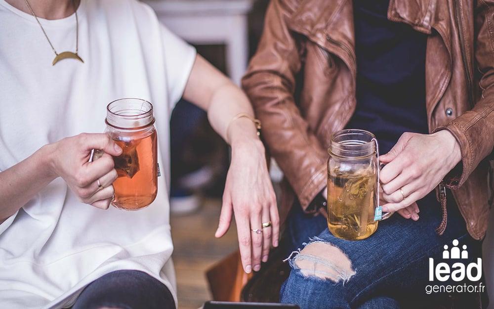 deux personnes buvant un verre de thé et aillant une discussion assis sur des chaises