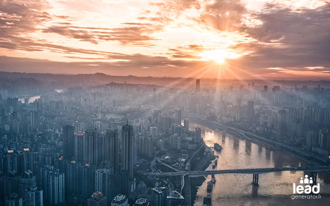 Ville moderne prise en photo dans les airs avec le lever du soleil derrière les nuages en arrière plan