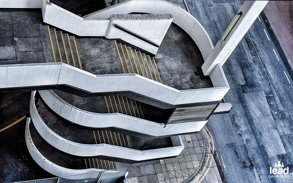 photo d'un escalier bétonné en colimaçon qui prend de la hauteur