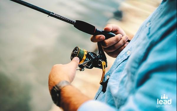homme tenant une canne à pèche et tournant la manivelle pour amener le poisson vers lui