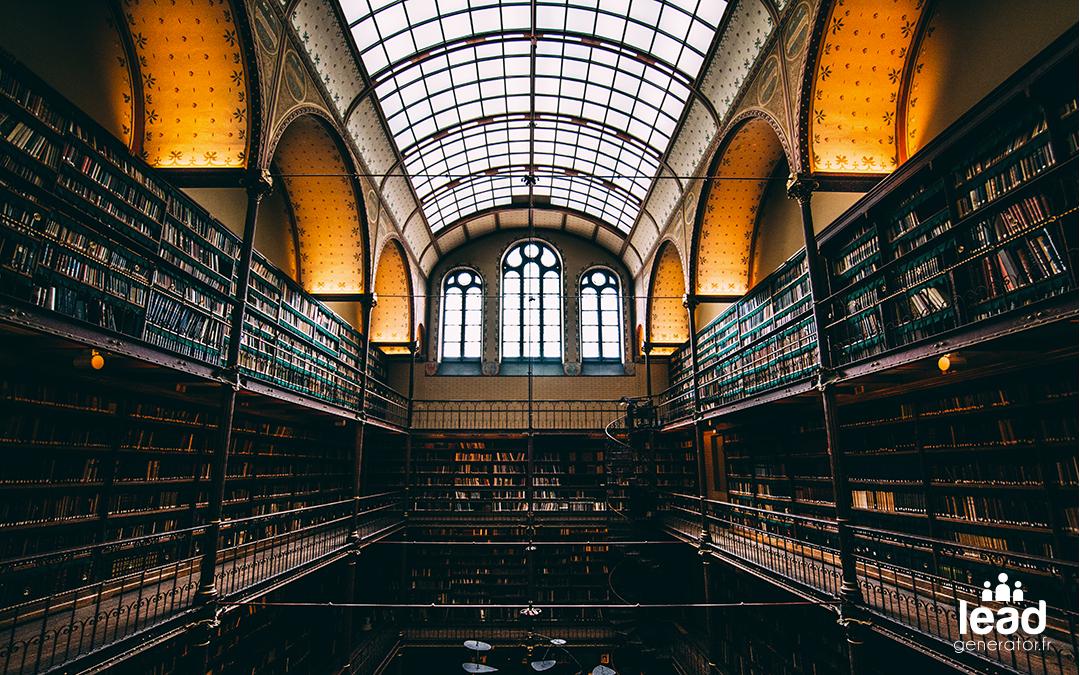 Une grande bibliothèque illuminé par le plafond en verre et les lumière sous les arches
