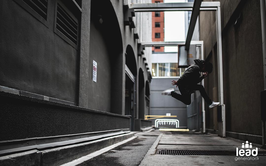 homme sautant en plein milieu d'une rue humide et sombre
