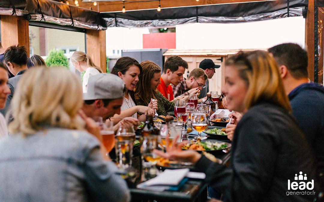 un groupe d'une dizaine de personne autour en train de parler autour d'une table dans un restaurant en terrasse