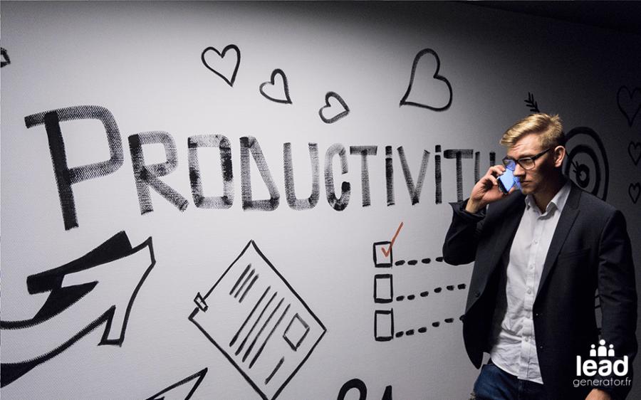 """Photo d'un homme avec téléphone sur fond de tableau blanc avec l'inscription """"productivité"""" pour imager la finalité de la prospection digitale"""