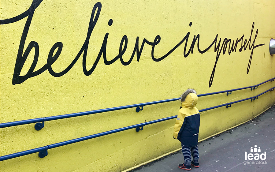"Photo d'un enfant debout devant un mur où est écrit ""believe in yourself"""