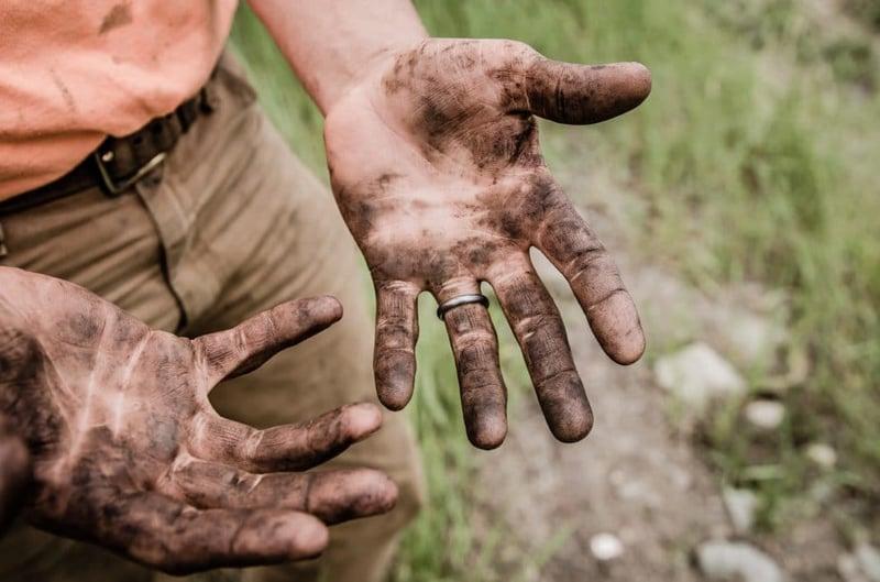 photo des mains sales d'un homme aillant travaillé avec la terre et la boue