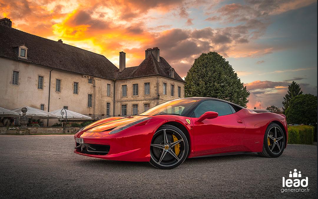 Ferrari rouge garé devant un grand bâtiment avec en arrière plan un couché de soleil
