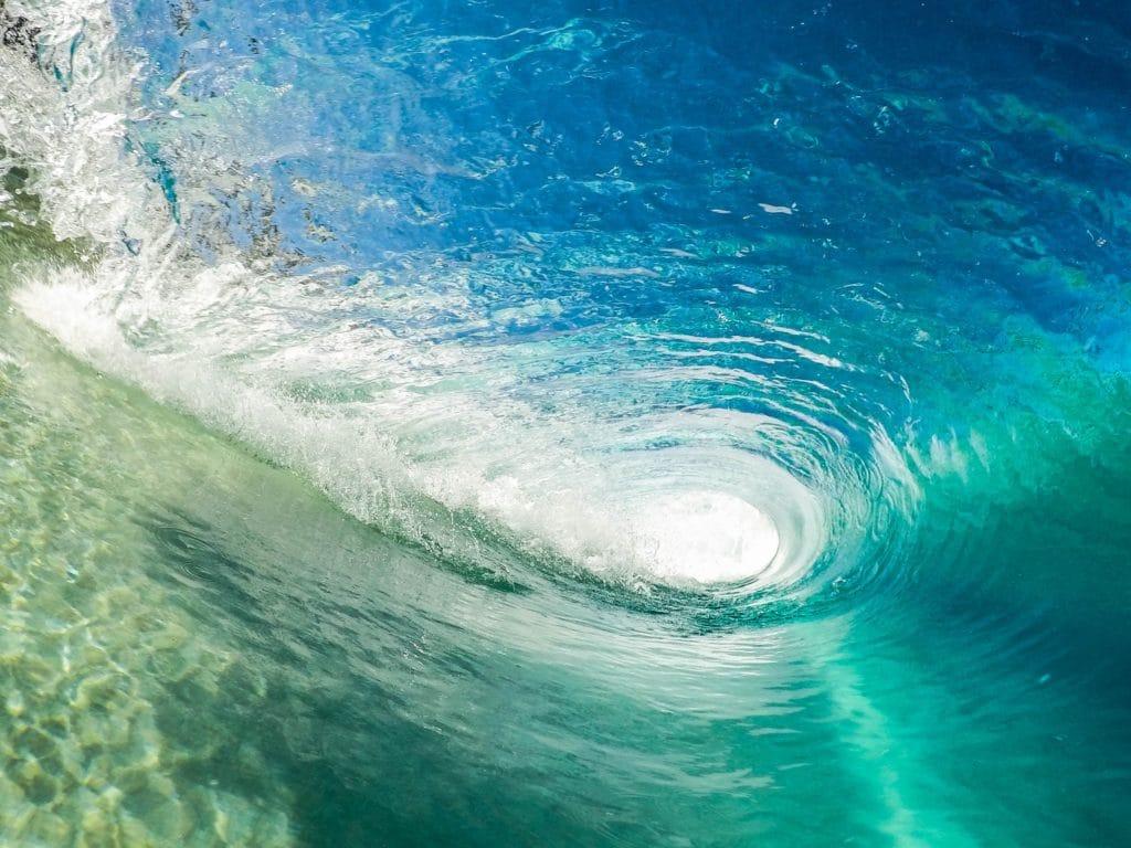 Photo de l'intérieur d'un rouleau de vague avec une eau de mer bleu turquoise