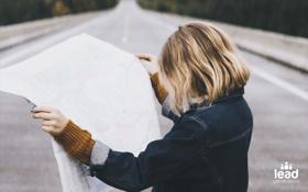 Photo d'une femme tenant une carte pour imager la définition de buyer journey en b2b