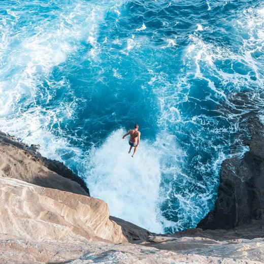 Homme qui plonge dans l'océan entouré de falaise